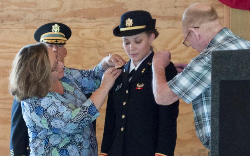 Abigail Vickery's parents – Michelle (left) and Rick (right) pin on the shoulder boards of a second lieutenant after their daughter was commissioned Saturday.