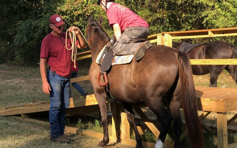 Apprentice Eli Troyer mounts horse Buckwheat under the advisement of Steadfast co-founder/journeyman Tod Bethea.