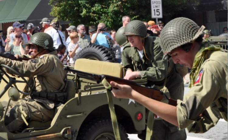 World War II re-enactors fire on a group of German re-enactors holding the Pond Street Bridge during the 2018 military weekend.