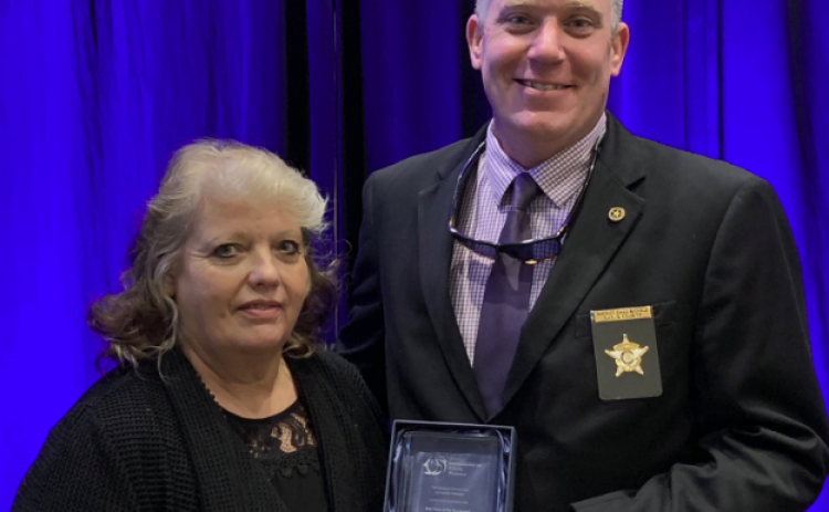 Rabun County Sheriff Chad Nichols, co-chair of the Mountain Judicial Circuit Family Violence Task Force, accepts the task force of the year award from Stephanie Woodard, chair of the Georgia Commission on Family Violence.