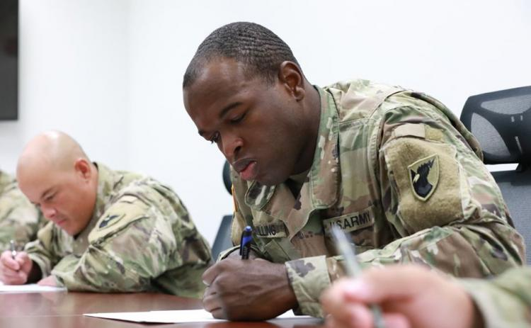 Army Spec. Isaac Swilling (right) concentrates on a test during a recent soldier of the year competition. Swilling is based at Andersen Air Force Base in Guam. He's the son of former SCHS standout Ken Swilling.