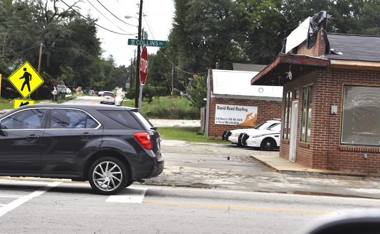 A pair of police cruisers peek out from behind the old Hemphill's Store building being turned into a Toccoa P.D. substation. Work on the building has been delayed, city manager Billy Morse said.