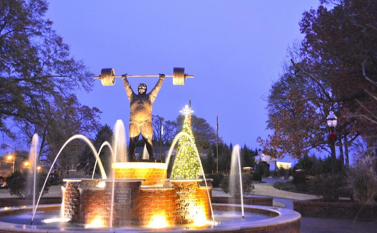 The Paul Anderson Memorial Park decorated for Christmas including the fountain in the foreground and Christmas tree in the background.